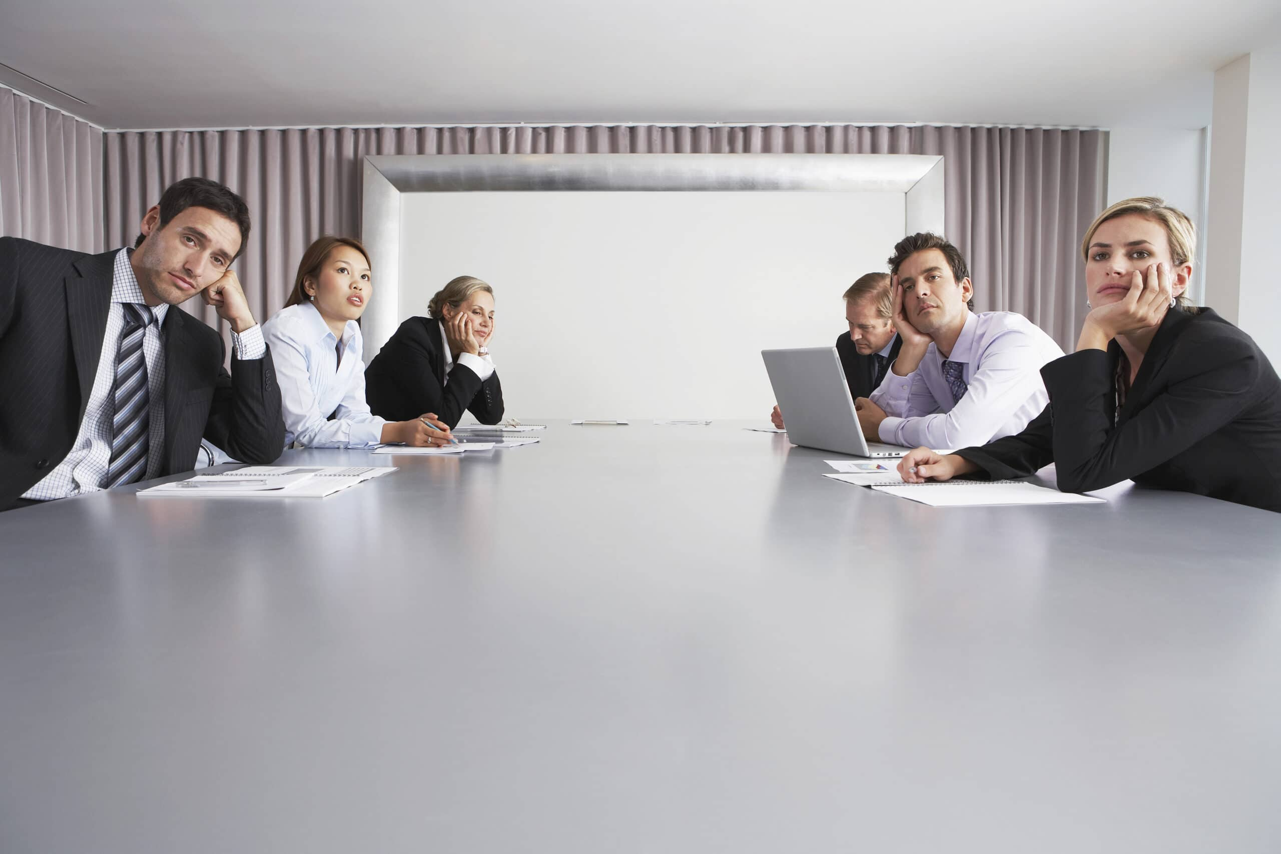 Bored multiethnic business people sitting in conference room