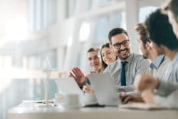 Happy businessman talking to colleagues around at a table at a boardroom of the future