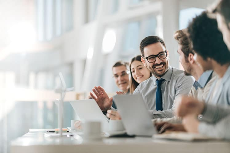 Happy businessman talking to colleagues around at a table