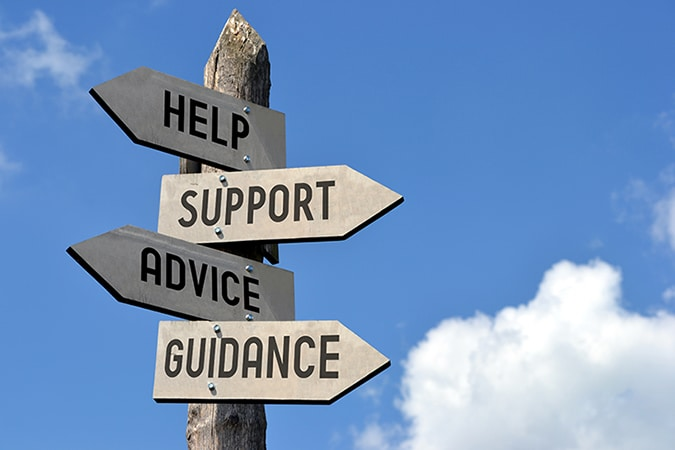 """Wooden singpost with """"help, support, advice, guidance"""" arrows against blue sky"""